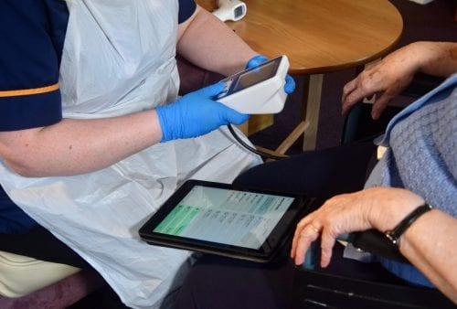 Doctor taking an elderly female's blood pressure