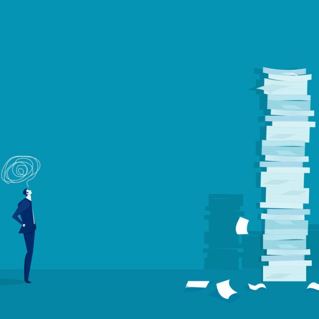 Man looking at stacks of papers piled up